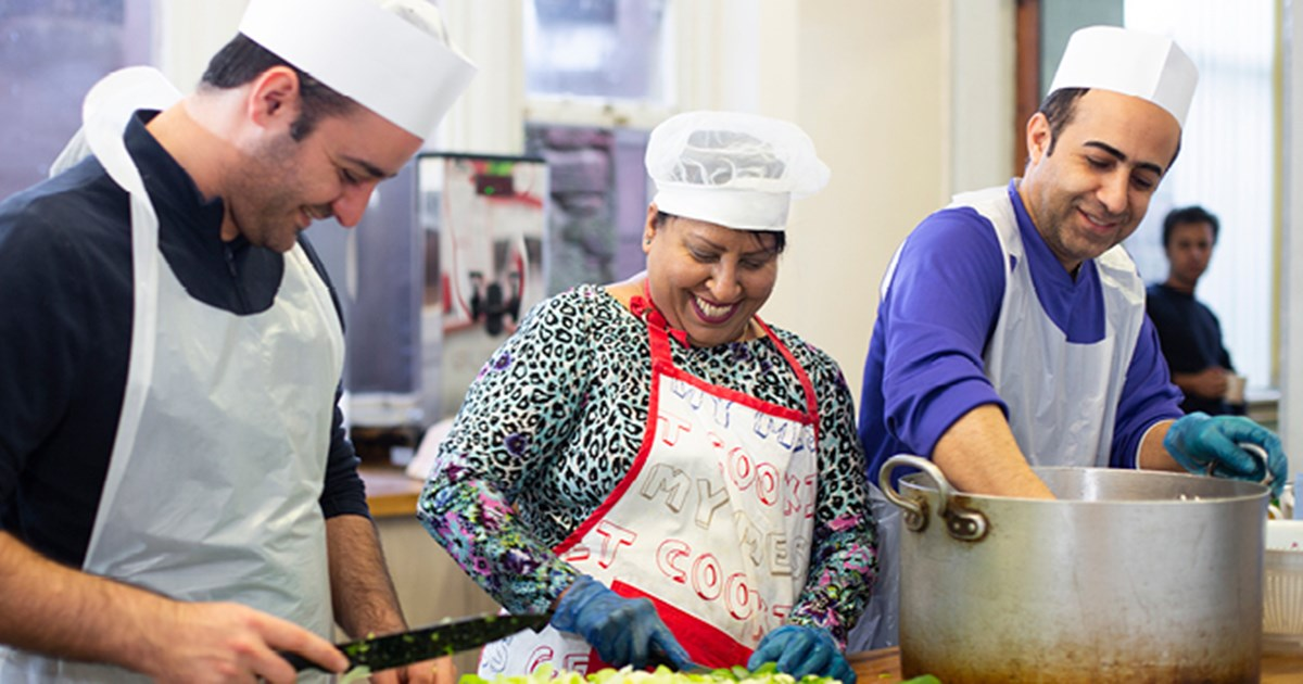A group of people at a cooking community event for Lloyds Bank Foundation