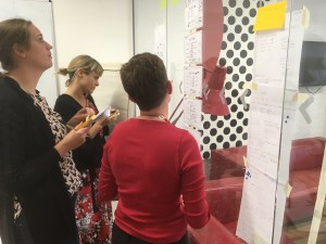 A group of WPNC staff in an internal workshop looking at a set of website design sketches