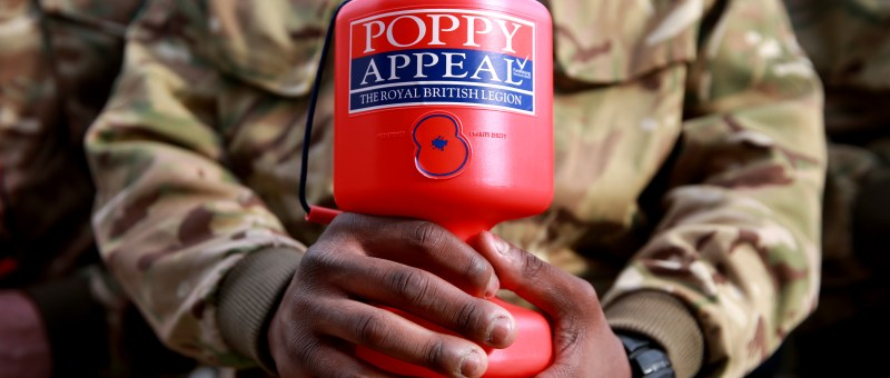 A member of the armed forces in army uniform holding a Royal British Legion Poppy Appeal collection tin