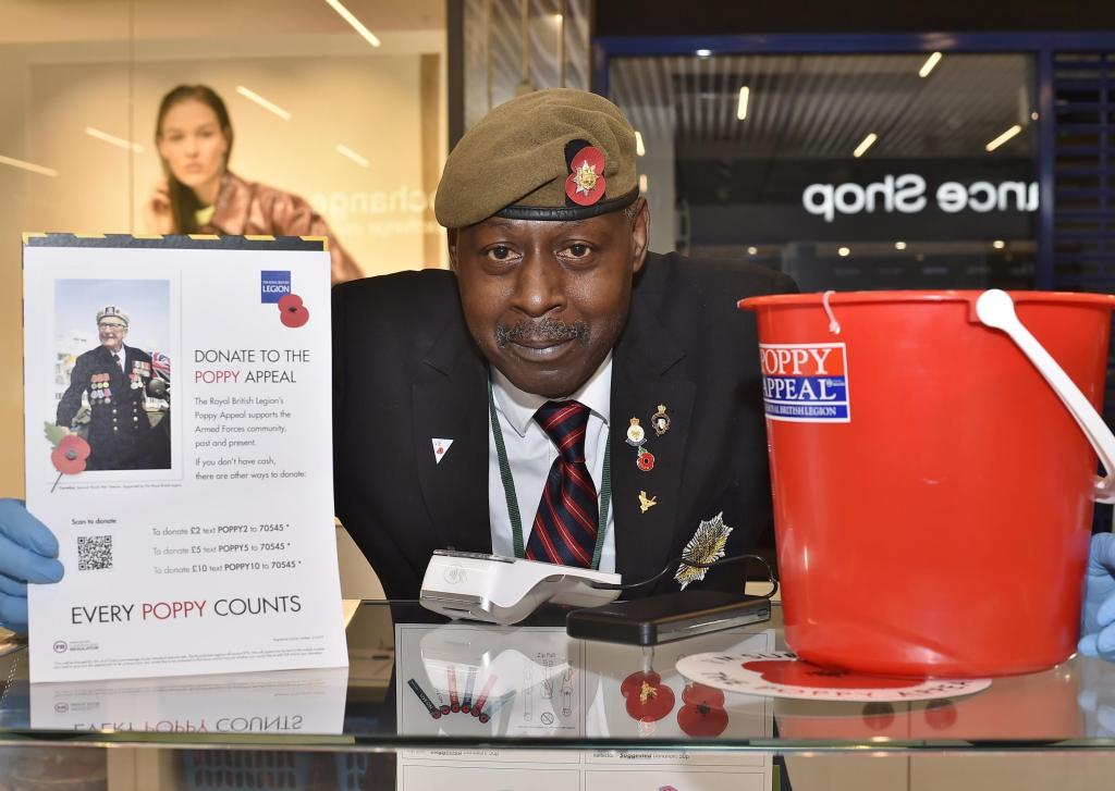 A Royal British Legion poppy collector with a collection tin and a poster with a QR code to donate