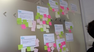 A set of user questions on a wall with post it note annotations