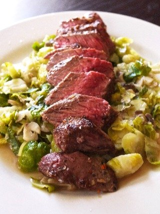 Image shows a dish of Skirt Steak with Brussels sprouts, leeks and chopped mushrooms cooked with truffle salt.