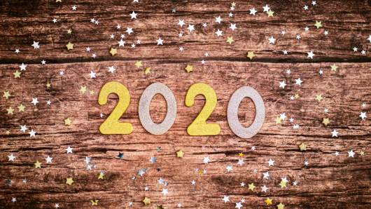 """""""2020"""" numbers laid over a wooden table with stars scattered around."""