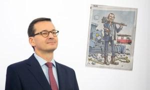 Karykatura Morawieckiego w zagranicznej gazecie. Premier z młotem i wyciągniętą ręką, w tle ruiny