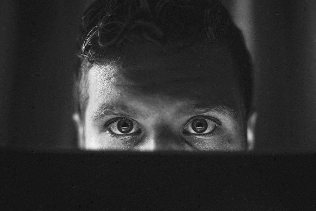 Online creeper peeking over computer