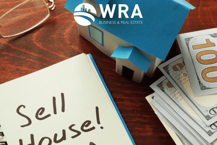 Imagem escrito venda da casa em inglês, com uma casa em miniatura, notas de cem dólares e um óculos de grau