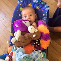 Baby in Bouncy Chair covered in toys