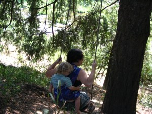 2006 Babywearing conference [Image: A white woman with short brown hair sits on a tree swing, facing away from the camera, her hands holding the ropes. Her blond 2 year old son with long, blonde hair is on her back in a Wrapsody Orion wrap, which is turquoise. They are both in shadow.]