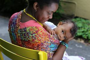 wrapsody-jennifer [image: A Black woman sits in a yellow chair facing away from the camera nursing her baby in a Wrapsody Hybrid wrap in Jennifer, which is multicolored with sunflowers. Her baby has dark brown skin and is gazing at the camera with interested eyes. His mother is gazing down at him.]