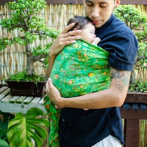 [image: A father with brown skin and hair is wearing his small baby on his front in a Wrapsody Tomorrow ring sling, which is green with yellow and red doodle-style semicolons. He is embracing his baby with his chin against the baby's forehead. The father is wearing a dark blue shirt and white shorts and standing in front of his bonsai garden.]