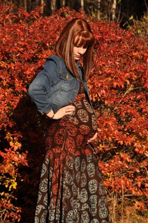 Image of a white woman with auburn hair wearing a brown dress with multi color Mexican sugar skulls pattern drop waist dress and denim jacket. She stands in front of a bush in full red autumn color with one hand under her pregnant belly.