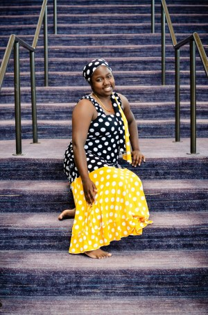 Image of a brown skin African American woman sitting on stone staircase wearing a drop waist dress with black bodice and yellow circle skirt with white polka dots. The dress is paired with a scarf in the same pattern the woman is wearing around the front of her hair.