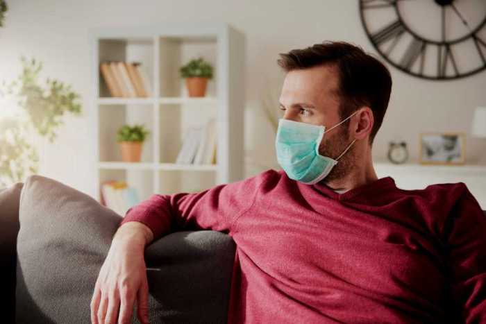 Man sitting on sofa in surgical mask