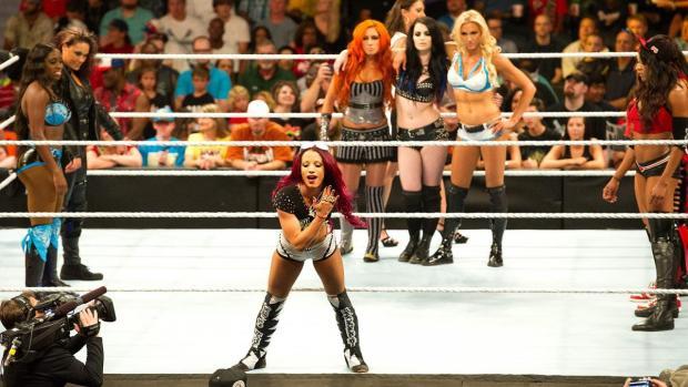 Sasha Banks está do lado de fora do ringue, segurando a segunda corda. Seu corpo está inclinado para a frente, enquanto ela coloca sua mão direita aberta a frente do seu rosto, mostrando seu anel, onde está escrito a palavra LEGIT.  Ao fundo estão as lutadoras Naomi, Tamina, Nikki e Brie Bella, Alicia Fox, Paige, Charlotte e Becky Lynch,