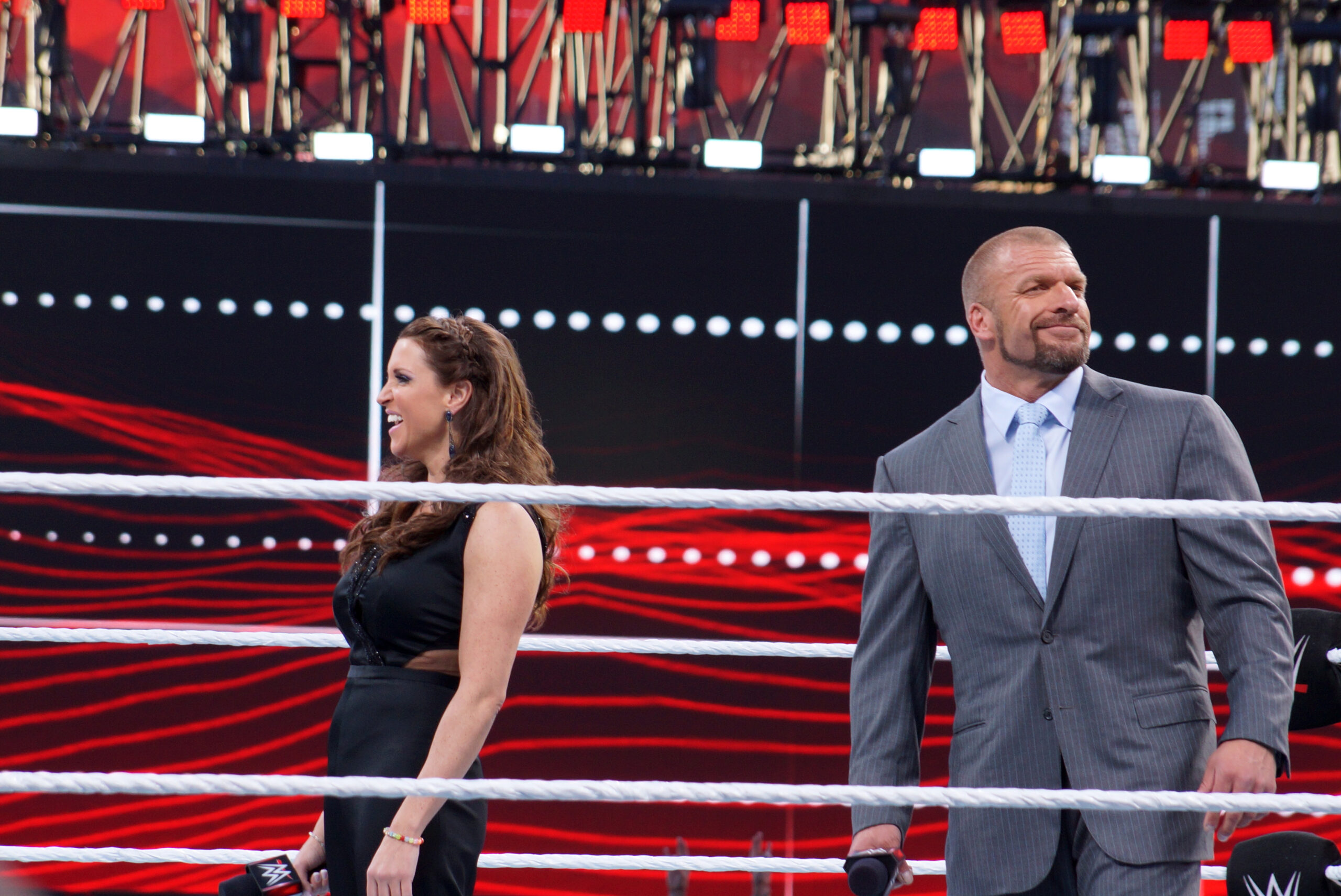 Triple H and Stephanie McMahon smile in the middle of the ring