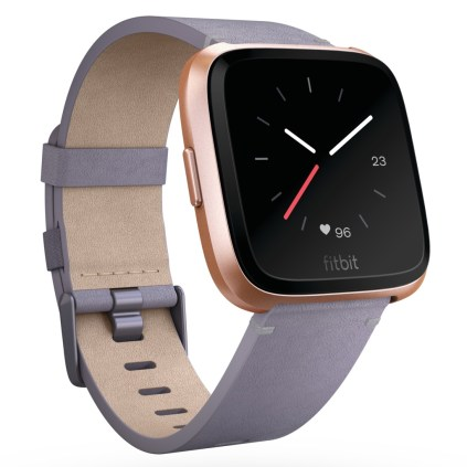 Product render of Fitbit Versa in 3 quarter view in Lavender Horween leather and rose gold case showing analog clock