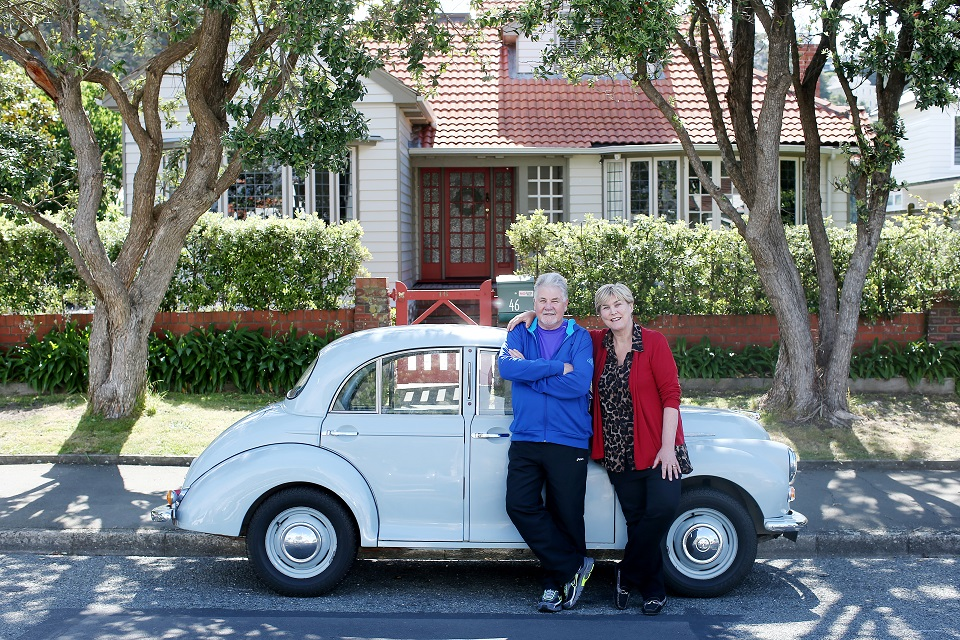 Image, older couple in front of nice car and house.