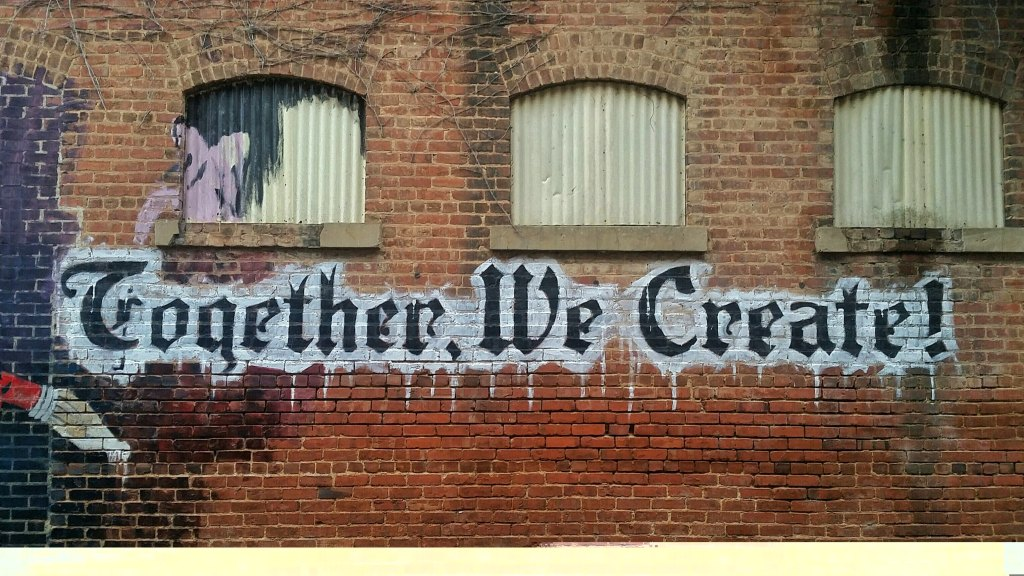 Image, Wall with 'Together we create' written on it.