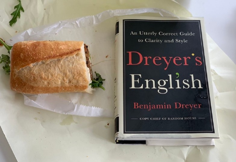 image, the cover of Dreyer's English by Benjamin Dreyer on a coffee table with a sandwich.