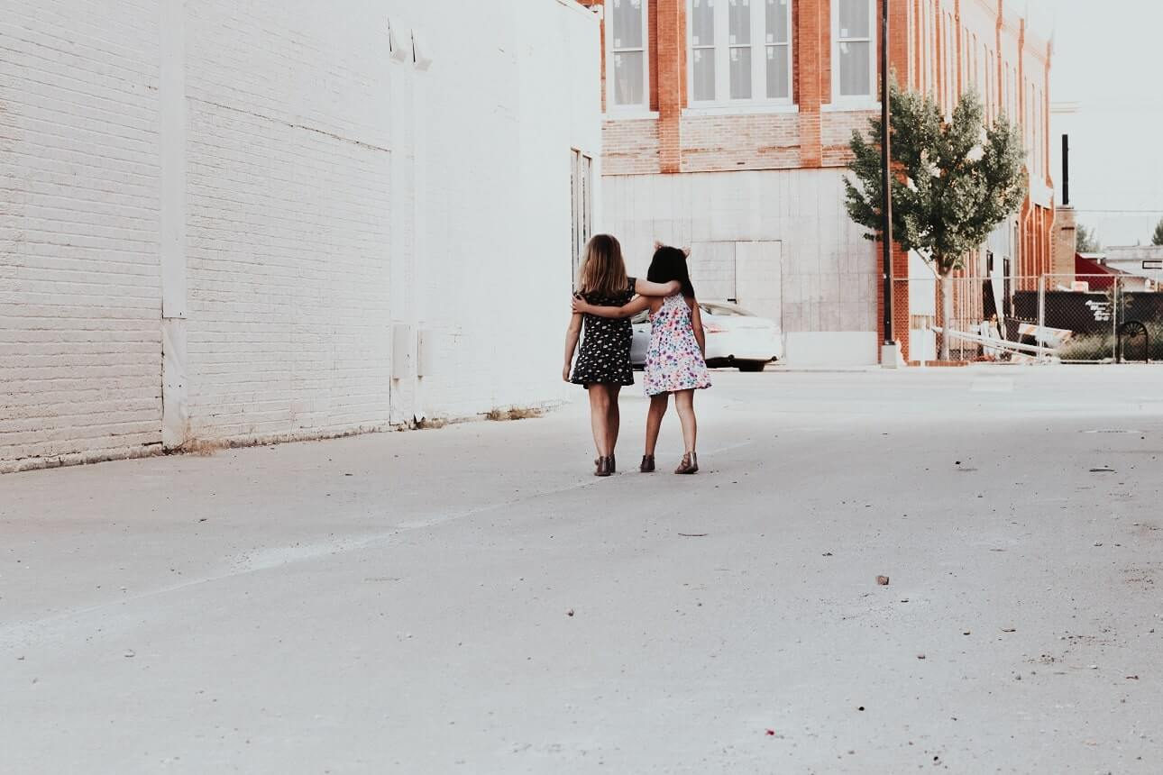 Image, two little girls walking down an alleyway with their arms around each other