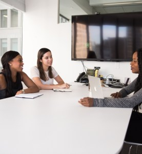three people meeting at table