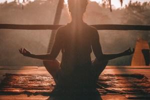 woman meditating outside at sunset or sunrise