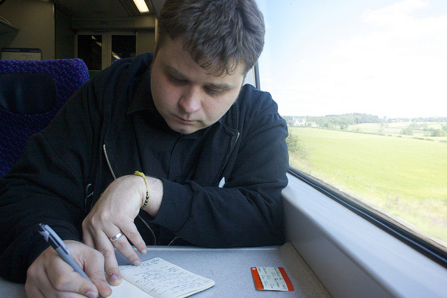 Young man writing notes in a train