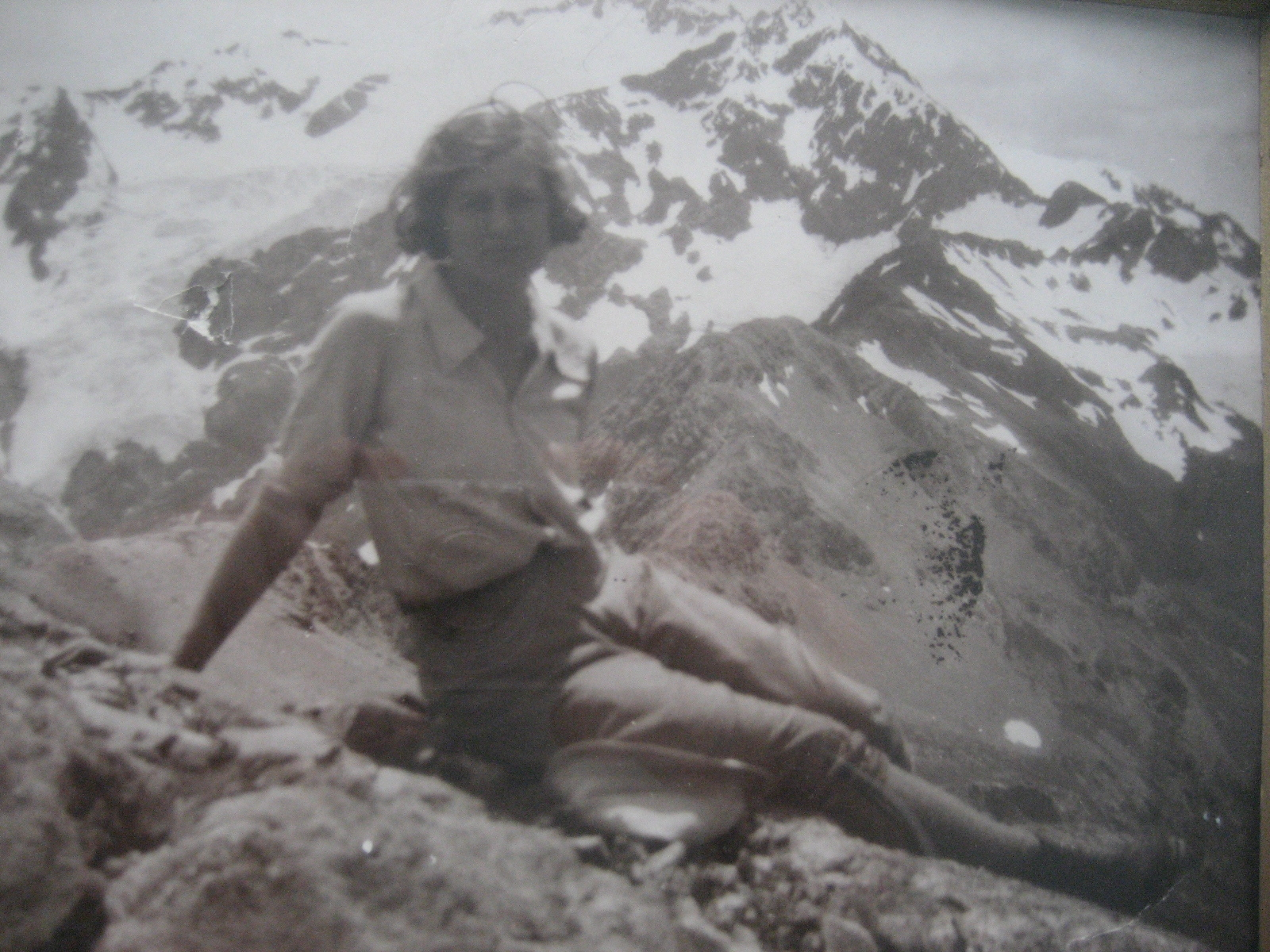 Celia Taylor relaxing on a mountain top in climbing gear.