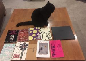 A cat named Ursula guarding ten books of poems and about poetry by Rachel McAlpine