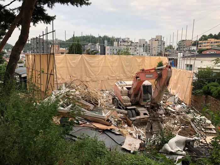 Bulldozer at work demolishing a house