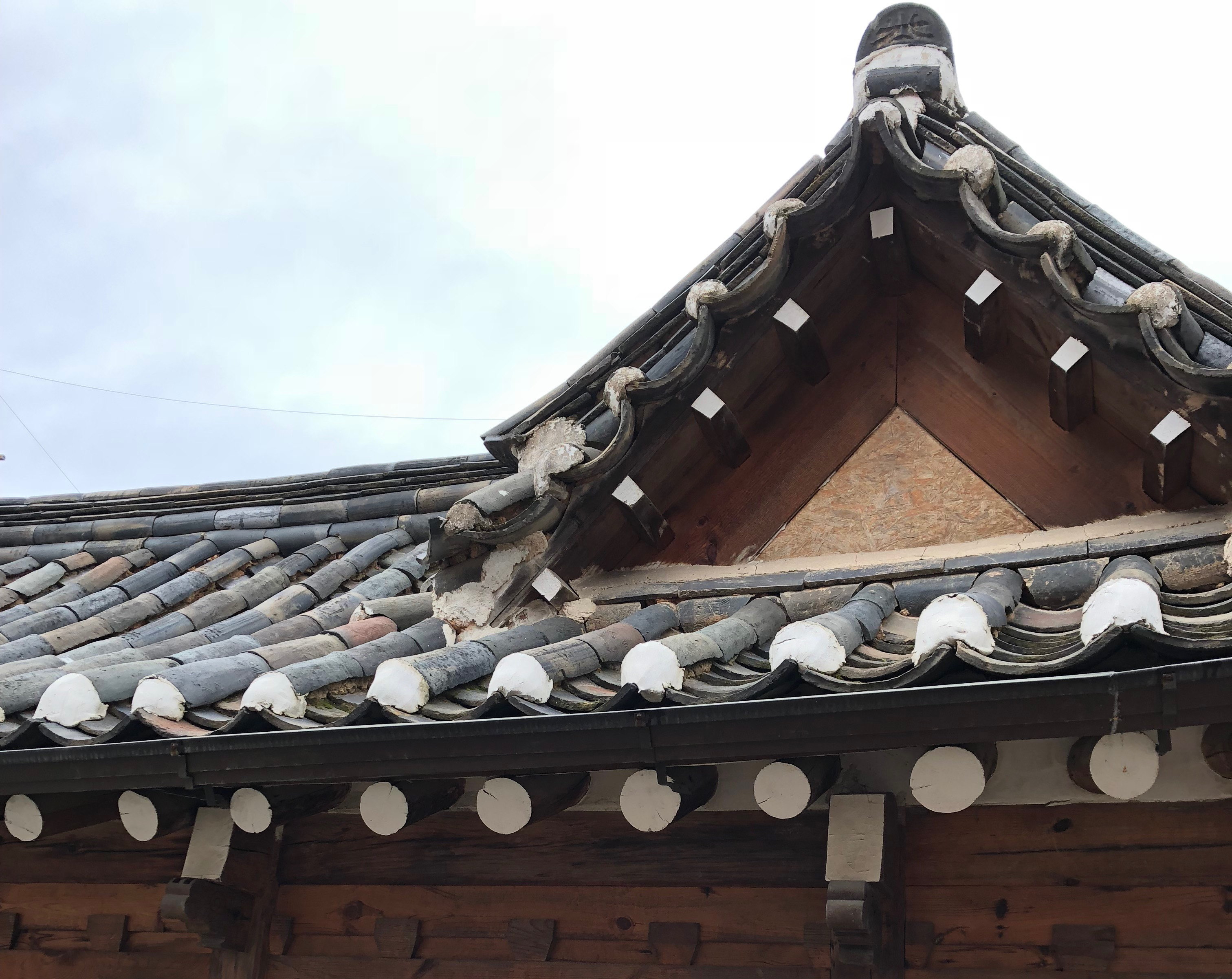 Traditional tiled roof on an old-style Korean house in Bukchon Hanok Village. Curved black tiles over white clay.