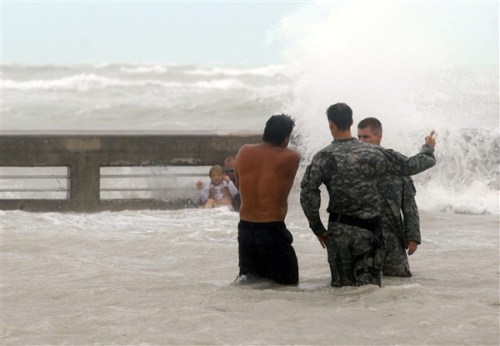 Soldiers talk to a man swimming in wild surf during Hurricane Ike. In the background a man holds a baby in the surf.