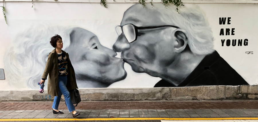 Billboard of two old lovers kissing. Text: WE ARE YOUNG