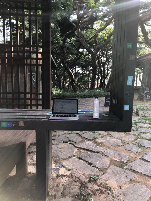 Outdoor seating in the grounds of Seoul Art Space—Yeonhui, with laptop and waterbottle.
