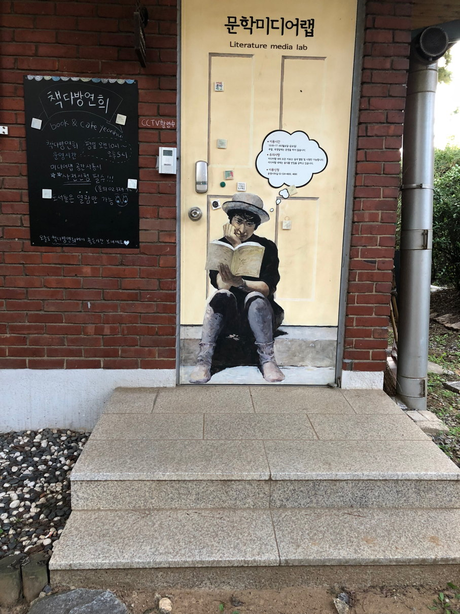 """A door with illustration of a person reading a book, marked """"Literature Media Lab"""" in English and Korean."""