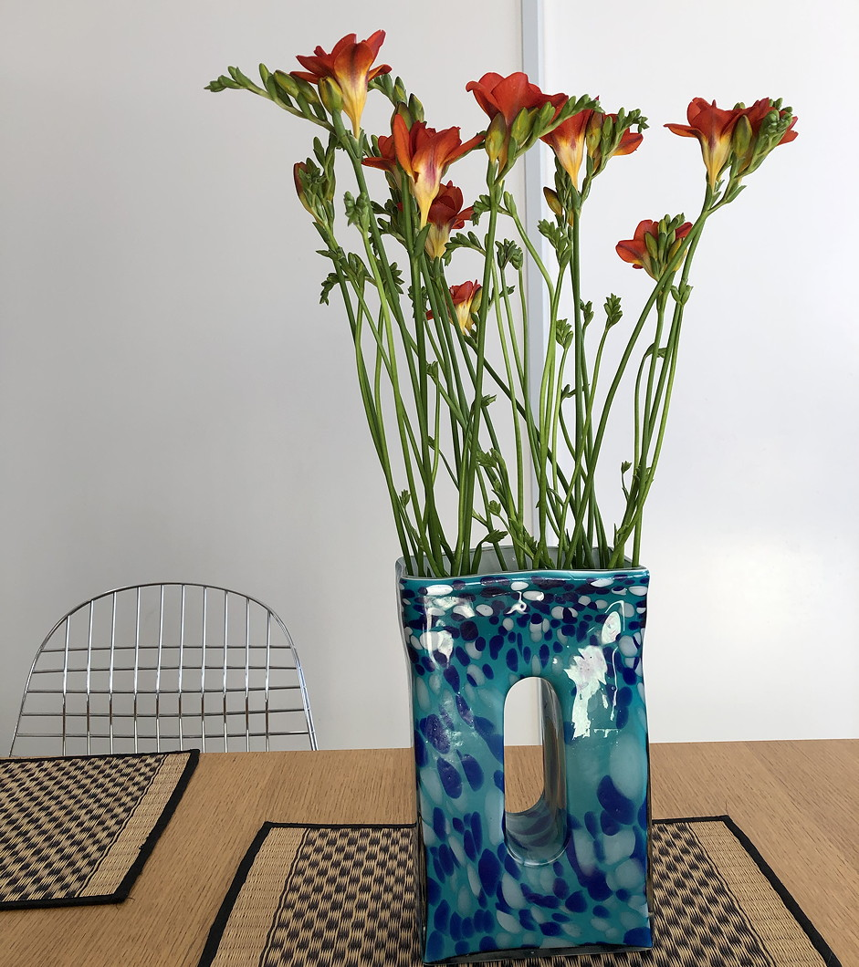 Orange freesias in a tall blue glass vase on a modern table.