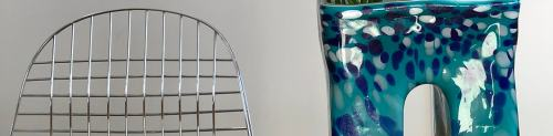 A wire chair and a handmade speckled blue vase