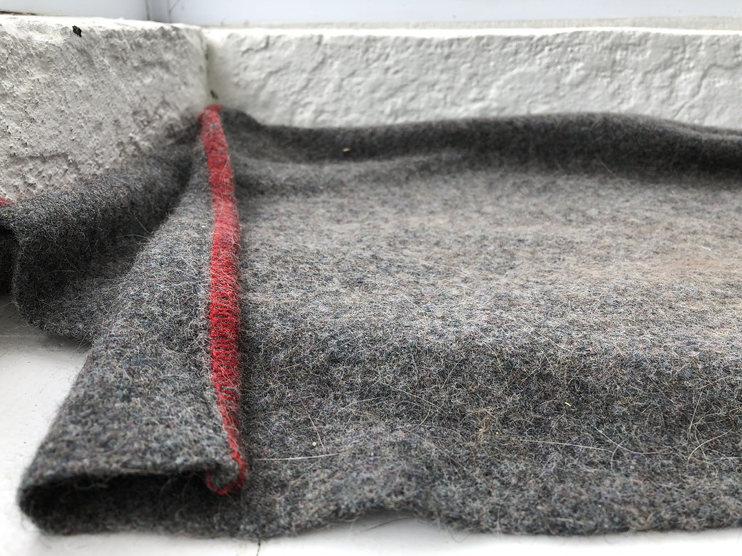 a dirty grey blanket covered in cat hair