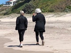 Two white-haired friends walking on a beach