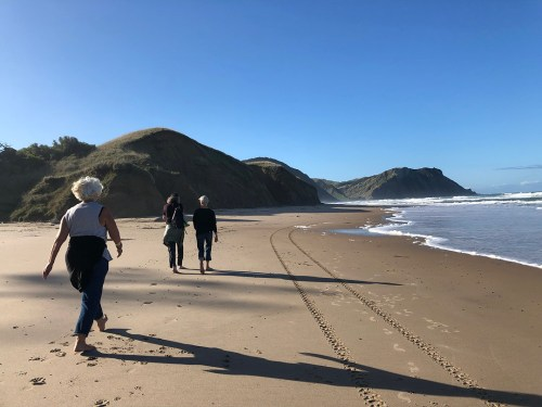 three women walking on a beach in New Zealand