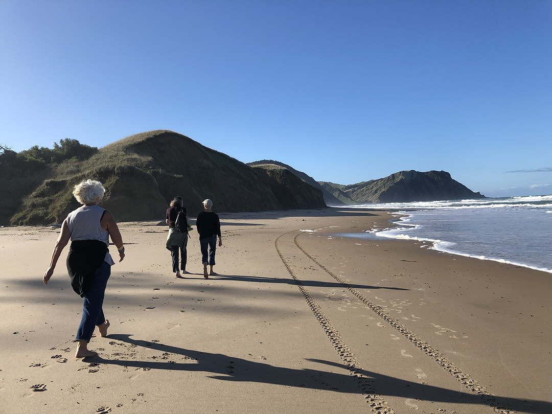 three women walking on a beach in New Zealand