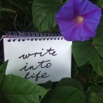 """write into life"" written on notebook nestled in morning glory with one purple flower"