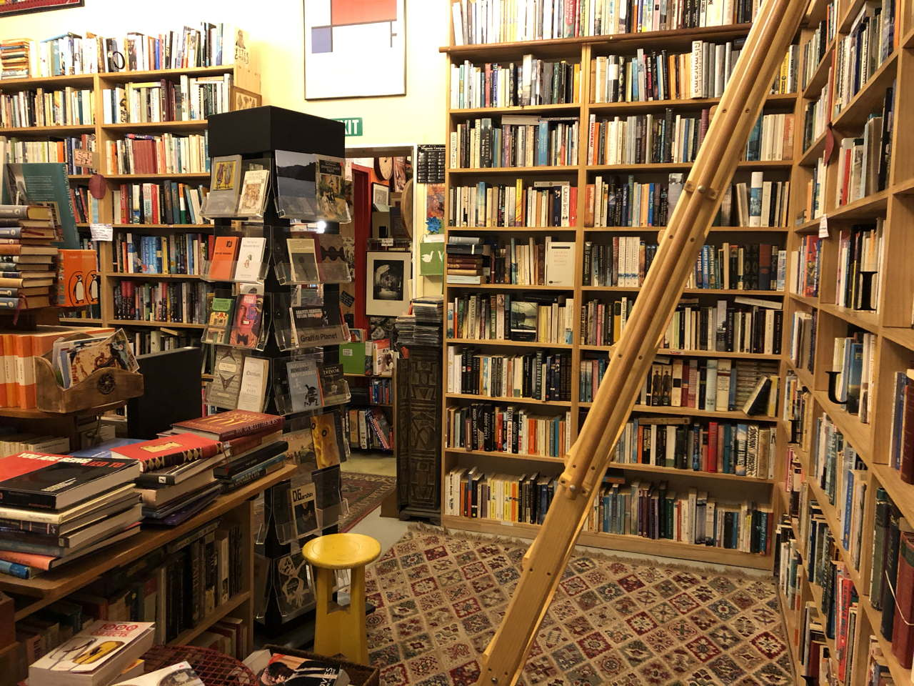 photo of a book store room. 9 shelves high stacked with books
