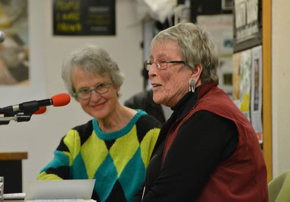 Rachel McAlpine listening, Mary Cresswell speaking into a microphone