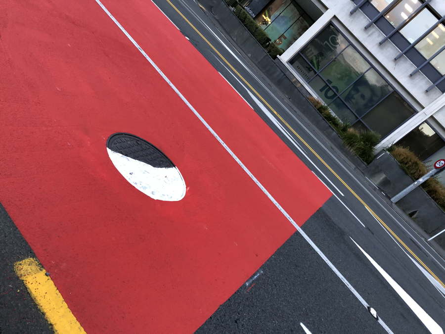 Crooked photo of a road. In a large red square is a manhole painted half black, half white