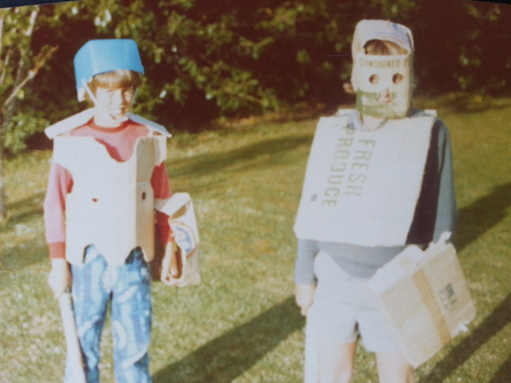 Blurry, faded colour photo of two boys dressed in cardboard armour.