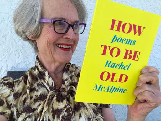 Cheerful woman holding a bright yellow and pink book called How To Be Old,Poems by Rachel McAlpine