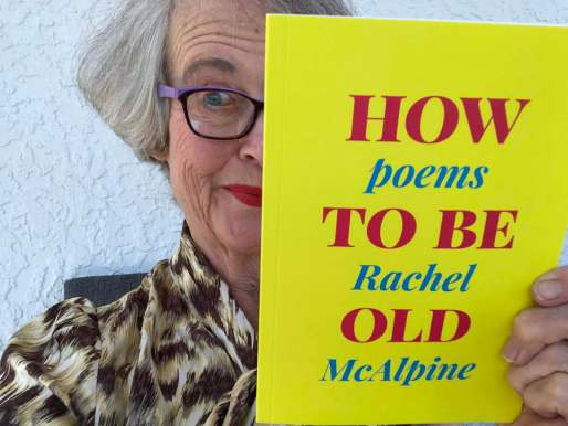 Dazed woman holding a bright yellow and pink book called How To Be Old,Poems by Rachel McAlpine