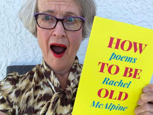 Shocked woman holding a bright yellow and pink book called How To Be Old, Poems by Rachel McAlpine