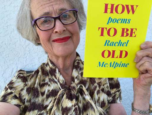 Old woman pretending to be tragic while holding a bright yellow and pink book called How To Be Old,Poems by Rachel McAlpine